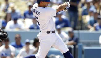 Los Angeles Dodgers' Austin Barnes watches his three-run home run against the Atlanta Braves during the fourth inning of a baseball game in Los Angeles, Sunday, July 23, 2017. (AP Photo/Alex Gallardo)