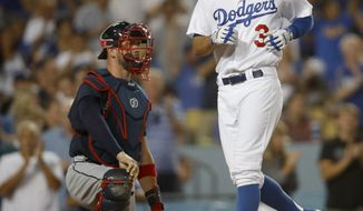 Los Angeles Dodgers' Chris Taylor, right, tags home plate after hitting a solo home run as Atlanta Braves catcher Tyler Flowers, left, watches during the seventh inning of a baseball game, Saturday, July 22, 2017, in Los Angeles. (AP Photo/Ryan Kang)
