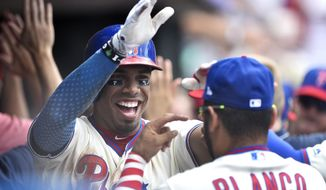 Philadelphia Phillies' Nick Williams, left, high fives Andres Blanco in the dugout after Williams hit a two-run home run off Milwaukee Brewers' Junior Guerra during the fourth inning of a baseball game, Sunday, July 23, 2017, in Philadelphia. (AP Photo/Derik Hamilton)