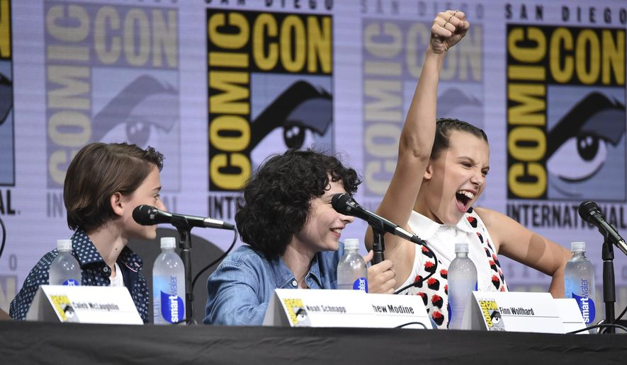 "Millie Bobby Brown, right, gestures as from left, Noah Schnapp, and Finn Wolfhard look on at the ""Stranger Things"" panel on day three of Comic-Con International on Saturday, July 22, 2017, in San Diego. (Photo by Richard Shotwell/Invision/AP)"