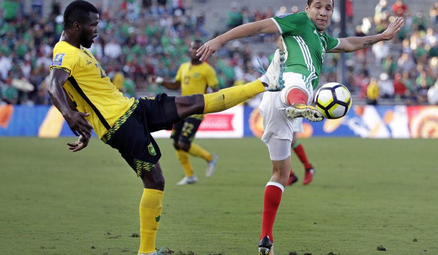 Jamaica's Kemar Lawrence, left, and Mexico's Jesus Duenas battle for the ball during the first half of a CONCACAF Gold Cup semifinal soccer match in Pasadena, Calif., Sunday, July 23, 2017. (AP Photo/Jae Hong)