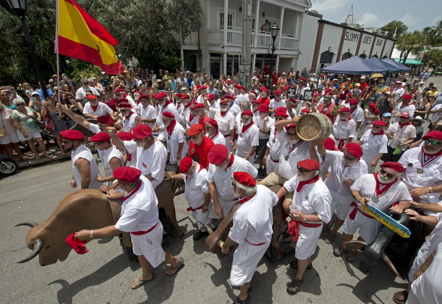 In this photo provided by the Florida Keys News Bureau, Ernest Hemingway look-alikes begin the Running of the Bulls Saturday, July 22, 2017, in Key West, Fla. The offbeat answer to the event's namesake in Pamplona, Spain, the activity was part of Key West's Hemingway Days festival. Hemingway lived in Key West in the 1930s and the island city's annual celebration continues through Sunday, July 23. (Andy Newman/Florida Keys News Bureau via AP)