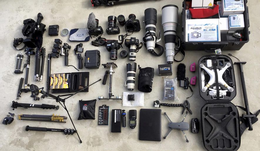 Photography and video equipment brought along by an Associated Press team on assignment aboard the Finnish icebreaker MSV Nordica is laid out on the ship's deck Saturday July 8, 2017, while sailing toward the Bering Strait in the North Pacific Ocean. The AP is accompanying a group of international researchers is sailing into the Arctic Sea aboard the Finnish icebreaker to traverse the Northwest Passage and record the environmental and social changes that are taking place in one of the most forbidding corners of the world. (AP Photo/David Goldman)