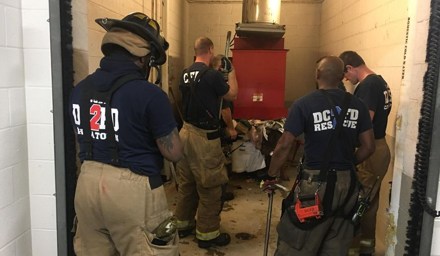 In this photo provided by DC Fire and EMS, emergency personnel respond to a call from a man who was stuck in a trash chute, early Sunday, July 23, 2017, in Washington. Spokesman Vito Maggiolo says the man was throwing out trash at the apartment building when he thought he dropped a cellphone in the chute. Maggiolo says the man leaned in to check and fell inside. (Vito Maggiolo/DC Fire and EMS Department via AP)
