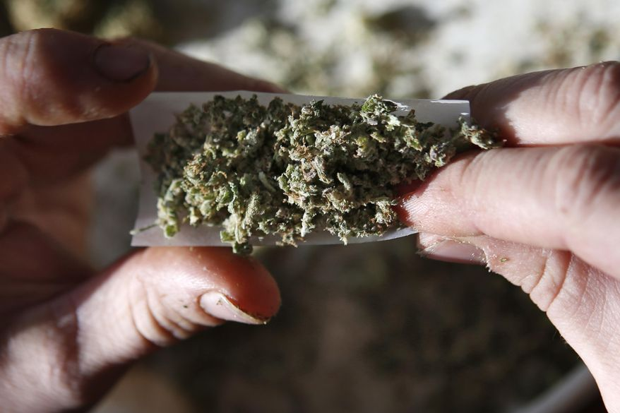 In this Nov. 21, 2014, file photo, medical marijuana is rolled into a joint in Belfast, Maine. (AP Photo/Robert F. Bukaty, file)