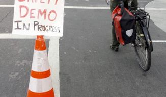 In this photo provided by the San Francisco Transformation Department, an orange cone separates cyclists from traffic on a San Francisco street on Monday, October 24, 2016. The divider was the work of the San Francisco Transformation Department, one of several like-minded groups of anonymous Twitter users who have taken a do-it-yourself approach to making road improvements in cities stretching from New York and Boston to Dallas.  (Twitter via AP)