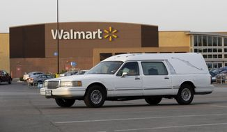 In this file photo, a hearse sits in the parking lot of a Walmart store where eight people were found dead in a tractor-trailer loaded with at least 30 others outside in stifling summer heat in what police are calling a horrific human trafficking case, Sunday, July 23, 2017, in San Antonio. (AP Photo/Eric Gay) **FILE**