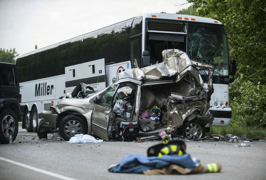 The wreckage of a minivan, in which one man and two women were killed, sits in front of a wrecked passenger bus after a crash involving five vehicles on North State Road 37 Business just north of Bayles Road in Bloomington, Ind. Saturday, July 22, 2017. (Alex McIntyre/The Herald-Times via AP)