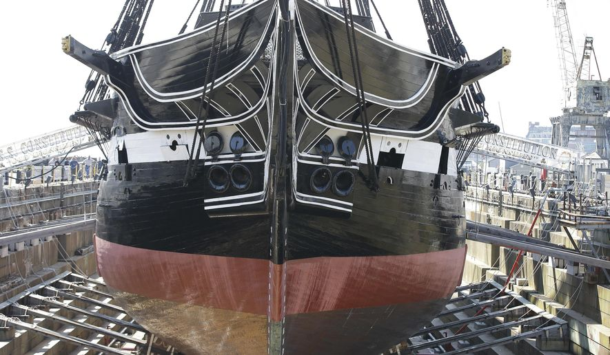 "In this Monday, July 17, 2017 photo Bob Gerosa, the 74th Commander of USS Constitution, ""Old Ironsides,"" the world's oldest commissioned warship, stands beside the vessel while it sits in dry dock after a more then two year long restoration. The ship is scheduled to be refloated overnight Sunday July 23, 2017 and be docked back at its berth Monday morning. (AP Photo/Stephan Savoia)"