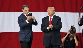 President Donald Trump looks over the crowd of scouts as Energy Secretary Rick Perry, left, uses his phone at the 2017 National Boy Scout Jamboree at the Summit in Glen Jean, W.Va., Monday, July 24, 2017. (AP Photo/Steve Helber)