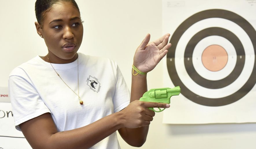In this May 27, 2017, photo, Marchelle Tigner, a firearms instructor, goes over a firearms safety tips during a class in Lawrenceville, Ga. Tigner's goal is to train 1 million women how to shoot a gun in her lifetime. She is among the nation's black women gun owners who say they are picking up firearms for self-protection. (AP Photo/Lisa Marie Pane)