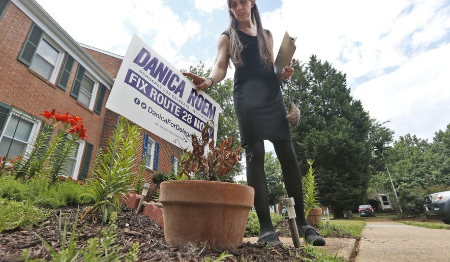 Democratic nominee for the House of Delegates 13th district seat, Danica Roem, places a campaign sign as she canvasses a neighborhood Wednesday, June 21, 2017, in Manassas, Va. Roem is running against Del. Bob Marshall in the 13th House of Delegates District. (AP Photo/Steve Helber)