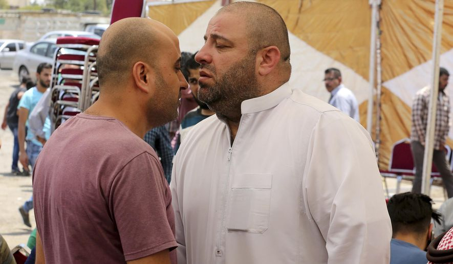 Zakaria al-Jawadah, right, the father of Mohammed Mohammed al-Jawawdeh, a 17-year-old Jordanian, who was killed on Sunday evening by an Israeli security guard who said he was attacked by him with a screwdriver, holds back his tears at a funeral tent in Amman, Jordan, Monday, July 24, 2017. The deadly shooting, that killed  two Jordanians at a residential building used by Israeli embassy staff in Jordan, has further complicated Israeli government efforts to find a way out of an escalating crisis over the Holy Land's most contested shrine. (AP Photo/Raad Adeleh)