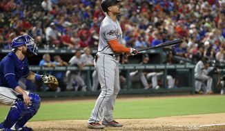 Miami Marlins right fielder Giancarlo Stanton (27) and Texas Rangers catcher Jonathan Lucroy (25) watch the flight of Stanton's second home run of the game during the eighth inning of a baseball game, Monday, July 24, 2017, in Arlington, Texas. (AP Photo/Jeffrey McWhorter)