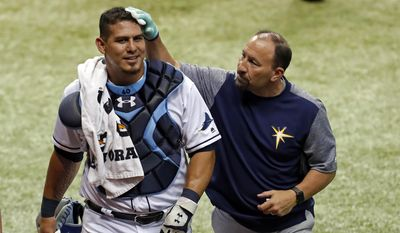 Tampa Bay Rays head athletic trainer Ron Porterfield, right, applies pressure to a cut on the head of Rays catcher Wilson Ramos who was struck by the broken bat of Baltimore Orioles' Ruben Tejada during the fifth inning of a baseball game Monday, July 24, 2017, in St. Petersburg, Fla. (AP Photo/Mike Carlson)