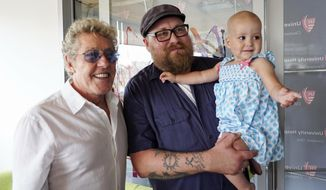 Roger Daltrey, lead singer for the English rock band The Who, left, poses with Adam Kirk and his daughter Sawyer McGhee, a cancer patient, in Cleveland, Ohio, on Monday, July 24, 2017.  (AP photo/Dake Kang)
