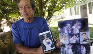 """In this July 10, 2017 photo, Clifford Kang, father of soldier Ikaika E. Kang, poses with photos of his son in Kailua, Hawaii. Ikaika E. Kang, an active-duty U.S. soldier, was arrested over the weekend on terrorism charges that accuse him of pledging allegiance to the Islamic State group and saying he wanted to """"kill a bunch of people."""" Ikaika E. Kang is scheduled to appear in federal court for an arraignment Monday, July 24, 2017. (Bruce Asato/The Star-Advertiser via AP)"""