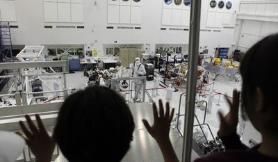 FILE - In this April 4, 2011, file photo, school children look from a viewing gallery at NASA engineers working on the rover Curiosity at the Mars Science Laboratory, at the Jet Propulsion Laboratory in Pasadena, Calif. (AP Photo/Damian Dovarganes, File)