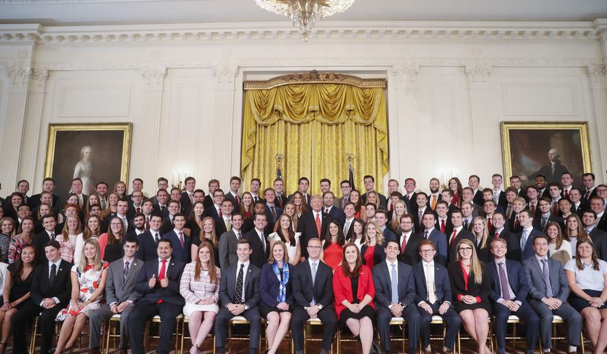 President Donald Trump, center, poses for a photo with outgoing White House interns in the East Room of the White House in Washington, Monday, July 24, 2017. (AP Photo/Pablo Martinez Monsivais)