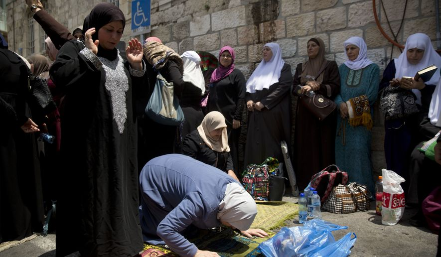 Palestinian women pray at the Lion's Gate following an appeal from clerics to pray in the streets instead of the Al Aqsa Mosque compound, in Jerusalem's Old City, Tuesday, July 25, 2017. Dozens of Muslims have prayed in the street outside a major Jerusalem shrine, heeding a call by clerics not to enter the site until a dispute with Israel over security arrangements is settled. This comes after Israel removed metal detectors earlier on Tuesday. (AP Photo/Oded Balilty)