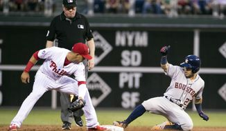 Houston Astros' Jose Altuve, right, slides into second base for a double as Philadelphia Phillies second baseman Cesar Hernandez, left, looks to apply the tag during the third inning of a baseball game, Monday, July 24, 2017, in Philadelphia. (AP Photo/Chris Szagola)