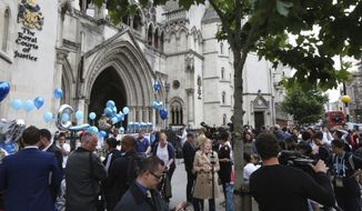 Supporters of critically ill baby Charlie Gard outside the High Court in London after his parents Connie Yates and Chris Gard spoke Monday, July 24, 2017. The parents of critically ill baby Charlie Gard wept as they dropped their legal bid Monday to send him to the United States for an experimental medical treatment, acknowledging that the window of opportunity to help him had closed.  (AP Photo/Caroline Spiezio)