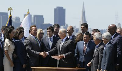 California Gov. Jerry Brown, right, shakes hands with former Gov. Arnold Schwarzenegger, left, after signing a climate bill on Treasure Island, Tuesday, July 25, 2017, in San Francisco. Gov. Brown signed legislation keeping alive California's signature initiative to fight global warming, which puts a cap and a price on climate-changing emissions. The Democratic governor was joined by his celebrity predecessor, Arnold Schwarzenegger, who signed the 2006 bill that led to the creation of the nation's only cap and trade system to reduce greenhouse gases in all industries. (AP Photo/Eric Risberg)