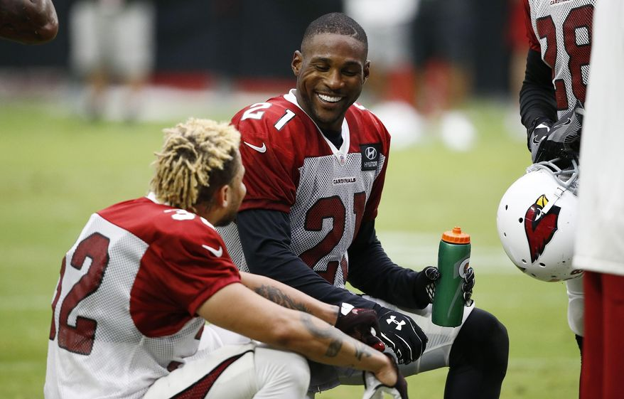Arizona Cardinals defensive backs Patrick Peterson (21) and Tyrann Mathieu (32) talk on the sideline during an NFL football training camp Monday, July 24, 2017, in Glendale, Ariz. (AP Photo/Ross D. Franklin)