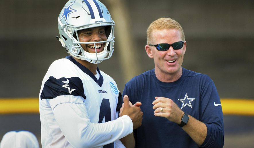 Dallas Cowboys quarterback Dak Prescott, left, and head coach Jason Garrett have fun after playing catch following practice at the NFL football team's training camp in Oxnard, Calif., Monday, July 24, 2017. (AP Photo/Michael Owen Baker)