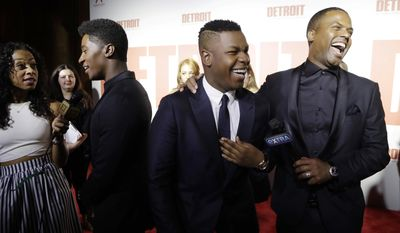 """John Boyega shares a laugh with Extra correspondent A.J. Calloway, right, as Joseph David Jones is interviewed on the red carpet before the premiere of """"Detroit"""" at the Fox Theatre, Tuesday, July 25, 2017, in Detroit. The movie, directed by Kathryn Bigelow is set in the summer of 1967 where rioting and civil unrest tore apart the city of Detroit. (AP Photo/Carlos Osorio)"""