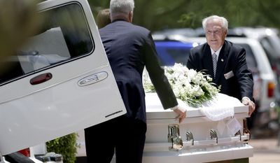 The caskets of family members who were killed in a flash flood are loaded into hearses outside St. Patrick Catholic Church, Tuesday, July 25, 2017, in Scottsdale, Ariz. Ten members of an extended Arizona family were killed earlier this month in flash flood while they celebrated a birthday. (AP Photo/Matt York)