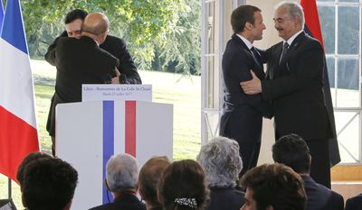 From left to right, Libya's Prime Minister Fayez al-Sarraj of the U.N.-backed government, Foreign Minister France's Jean-Yves Le Drian President Emmanuel Macron, General Khalifa Hifter of the Egyptian-backed commander of Libya's self-styled national army hug each other after a media conference at the Chateau of the La Celle-Saint-Cloud, west of Paris, France, Tuesday, July 25, 2017. President Emmanuel Macron is hosting a meeting of the two main rival leaders of chaotic Libya, trying to play peacemaker in a country where the stakes are high for both Europe and Africa. (AP Photo/Michel Euler)