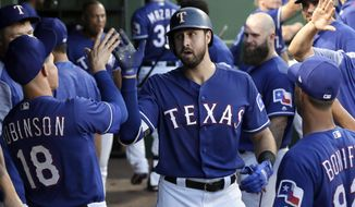 Texas Rangers' Joey Gallo, center, is congratulated by Drew Robinson (18) and others in the dugout after hitting a solo hoe run during the fourth inning of the team's baseball game against the Miami Marlins on Tuesday, July 25, 2017, in Arlington, Texas. (AP Photo/Tony Gutierrez)