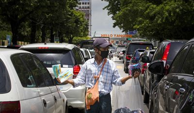 A street vendor sells masks to motorists to protect against the swine flu, Tuesday, July 25, 2017, in Yangon, Myanmar. Public health officials in Myanmar say that H1N1 flu, also known as swine flu, has killed three people out of 13 confirmed cases of the infection. (AP Photo/Thein Zaw)