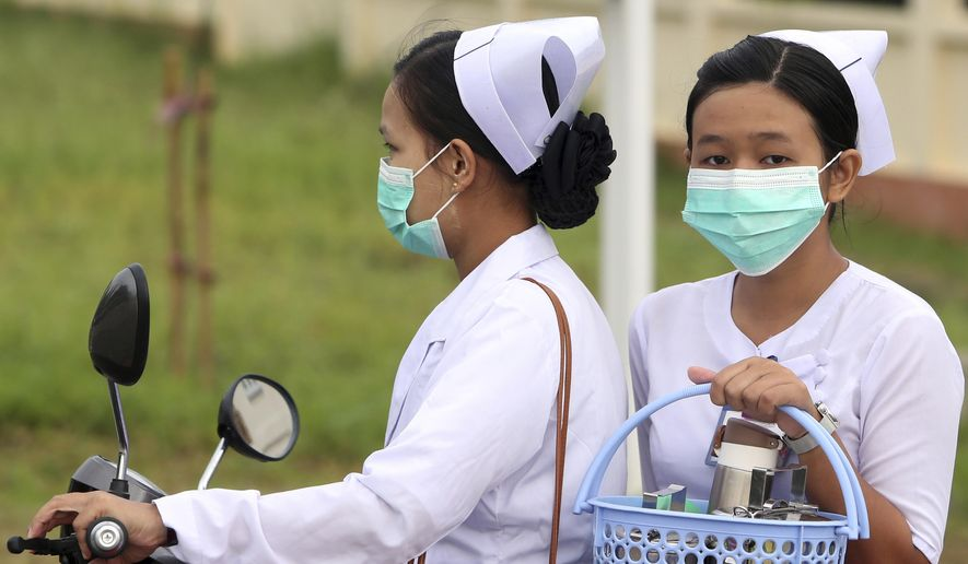 Nurses cover their faces with masks to protect from the spread of the swine flu outside the Naypyitaw hospital, Tuesday, July 25, 2017, in Naypyitaw, Myanmar. Public health officials in Myanmar say that H1N1 flu, also known as swine flu, has killed three people out of 13 confirmed cases of the infection. (AP Photo/Aung Shine Oo)