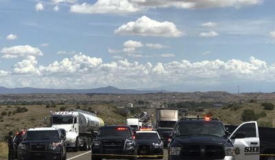 This photo provided by the New Mexico State Police show the scene on Interstate 25 north of Albuquerque, N.M., Tuesday, July 25, 2017, where there was a shootout between an armed robbery suspect and law enforcement officers. Gunfire between the suspect and New Mexico officers left a stolen truck and police vehicles shot up with bullet holes but nobody was injured. (Elizabeth Armijo/New Mexico State Police via AP)