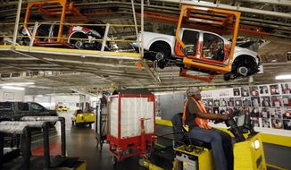 FILE - In this April 6, 2016, file photograph, vehicles are suspended above other installation stations as they are moved along the assembly line at the Nissan Canton Vehicle Assembly Plant in Canton, Miss. A bid by workers at Mississippi's Nissan Motor Co. plant for United Auto Workers representation could turn on a key voting bloc: the 1,500 Nissan employees who were initially hired through contract labor agencies. (AP Photo/Rogelio V. Solis, File)