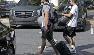 Carolina Panthers' Greg Olsen, left foreground, carries personal items from his car as he walks to the dorms as the NFL team's players arrive for the beginning of training camp at Wofford College in Spartanburg, S.C., Tuesday, July 25, 2017. The team has several issues looming including how much Cam Newton will throw and whether Thomas Davis and Greg Olsen will receive contract extensions. (AP Photo/Chuck Burton)