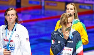 Italy's Federica Pellegrini kisses her gold medal as U.S. silver medal winner Katie Ledecky (left) looks on after the women's 200-meter freestyle final on Wednesday. (Associated Press)