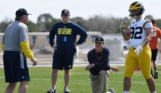 "Michigan coach Jim Harbaugh (kneeling) said the NCAA's plan to prevent teams from holding multiple practices with contact in one day ""makes all the sense in the world."" (Associated Press)"