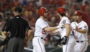 Washington Nationals' Bryce Harper, second from right, is restrained by Daniel Murphy (20) and third base coach Bob Henley, right, as he argues after he was ejected from the baseball game after he struck out during the eighth inning against the Milwaukee Brewers, Wednesday, July 26, 2017, in Washington. The Nationals won 8-5. (AP Photo/Nick Wass)