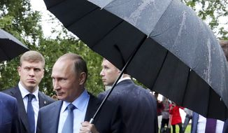 Russian President Vladimir Putin holds an umbrella as he looks at an outdoor fitness equipment installed on the Onezhskaya Embankment in Petrozavodsk, Russia, Wednesday, July 26, 2017. (Mikhail Klimentyev, Sputnik, Kremlin Pool Photo via AP)