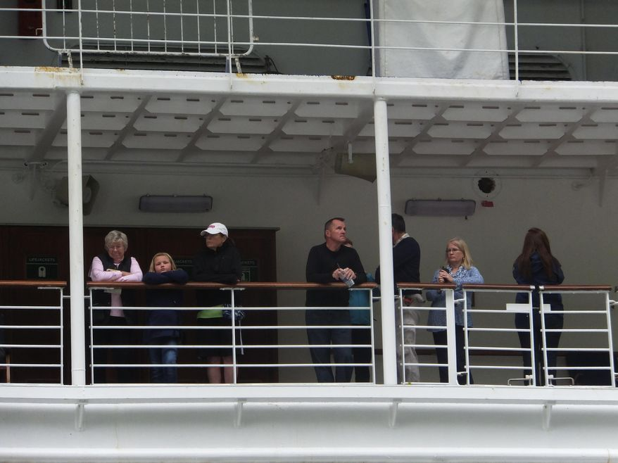 Several passengers of the Emerald Princess cruise ship bide their time on deck while waiting to disembark on Wednesday, July 26, 2017, in Juneau, Alaska. The FBI is investigating the domestic dispute death of a Utah woman on board the ship, which was traveling in U.S. waters outside Alaska. (AP Photo/Becky Bohrer)