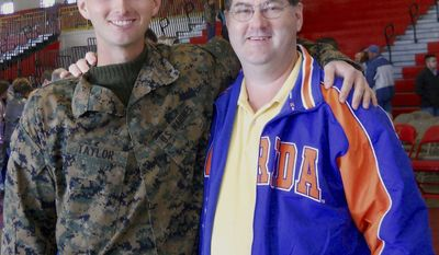 In this undated photo provided by David Taylor Sr., he poses with his son David Taylor, left, a former Marine. Taylor Sr. told The Associated Press on Tuesday, July 25, 2017, that he was notified by the U.S. State Department that his son was killed earlier this month in Syria while fighting for a Kurdish militia battling the Islamic State group. (Courtesy of David Taylor Sr. via AP)