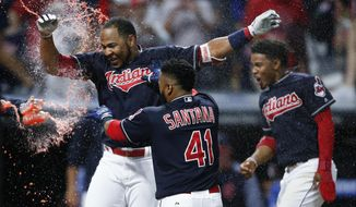 Cleveland Indians' Edwin Encarnacion, left, celebrates with Carlos Santana (41) and Francisco Lindor after hitting a game-winning grand slam off Los Angeles Angels' Bud Norris during the 11th inning of a baseball game, Tuesday, July 25, 2017, in Cleveland. The Indians won 11-7. (AP Photo/Ron Schwane)