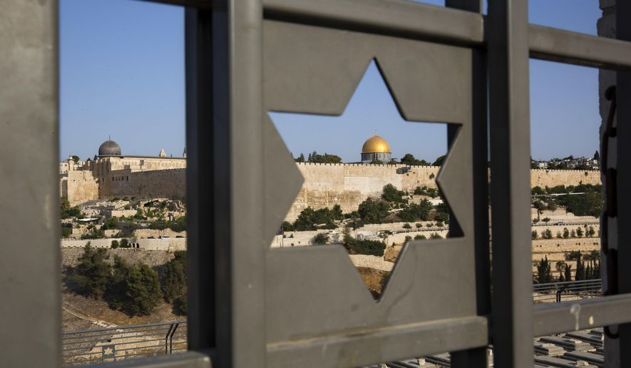 Jerusalem's Old City is seen trough a door with the shape of star of David, Tuesday, July 25, 2017. Israel has begun dismantling metal detectors it installed a week earlier at the gates of a contested Jerusalem shrine, amid widespread Muslim protests. (AP Photo/Oded Balilty)
