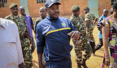 FILE - In this Tuesday, July 21, 2015 file photo, Burundi's President Pierre Nkurunziza walks to a polling station to cast his vote for the presidential election, in his hometown of Ngozi, Burundi. Hundreds of people have been killed and hundreds of thousands have fled the small East African nation in the two years since President Pierre Nkurunziza set off protests by declaring he would seek another term. (AP Photo/Berthier Mugiraneza, File)