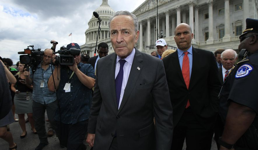 Senate Minority Leader Chuck Schumer of N.Y., leads fellow Democratic Senators to meet supporters outside the Capitol in Washington, Tuesday, July 25, 2017, after the Senate voted to start debating Republican legislation to tear down much of the Obama health care law. (AP Photo/Manuel Balce Ceneta)