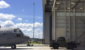 One of the eight C-130 cargo planes assigned to the Connecticut Air National Guard is towed into a new maintenance facility at the Bradley Air National Guard Base, Wednesday, July 26, 2017, in East Granby, Conn. Dignitaries were on hand to mark the opening of the new, $14.3 million, federally funded facility for the aircraft, which have been stationed in Connecticut since 2013 after the state's flying mission was in limbo. (AP Photo/Susan Haigh)
