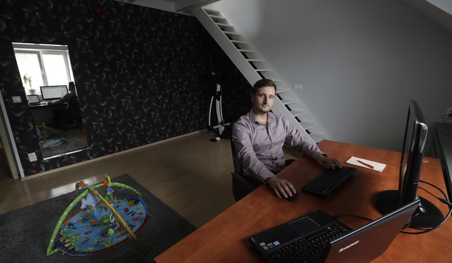 In this Tuesday, July 25, 2017, photo, Vilem Prochazka, an employee of Boston-based software company KangoGift, poses for a photo while sitting at his computer at his home in Kolin, Czech Republic. At some small businesses, the traditional chat around the watercooler takes place online and meetings are held via Skype, as staffers are working at home. (AP Photo/Petr David Josek)